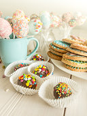 Toned shot of colorful candies, cup and cookies on table