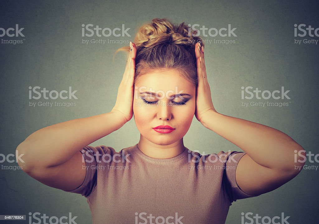 Too loud sound. woman covering ears with hands stock photo