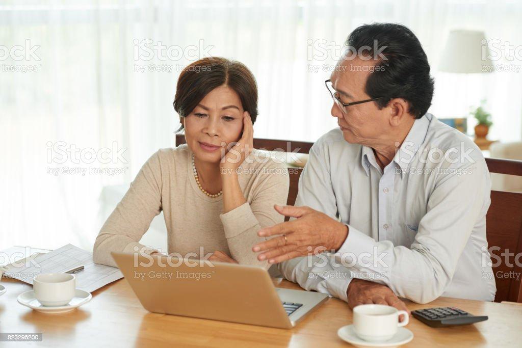 Unhappy Vietnamese senior couple discussing family budget