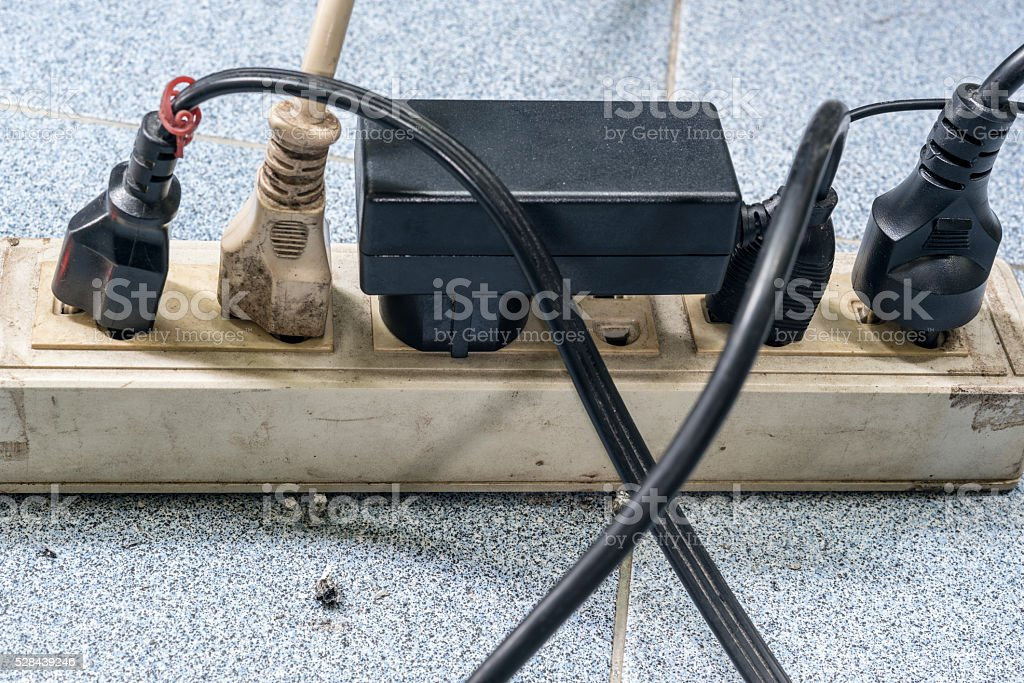 Too many plugs in a dirty socket stock photo