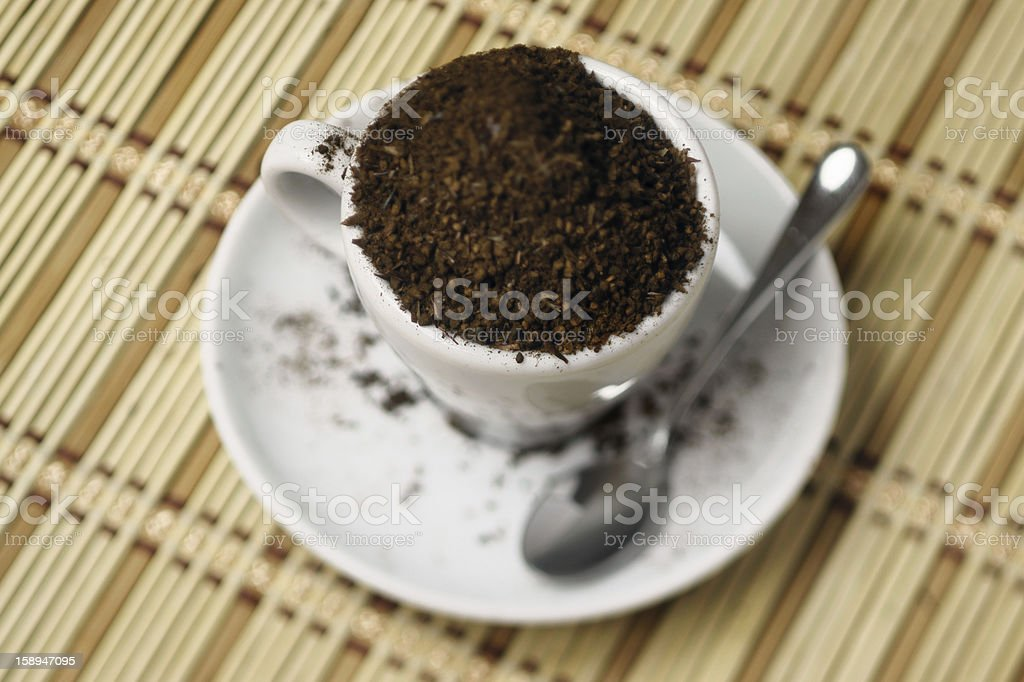 Too much coffee (gound, overflowing from a cup), blurred vision stock photo
