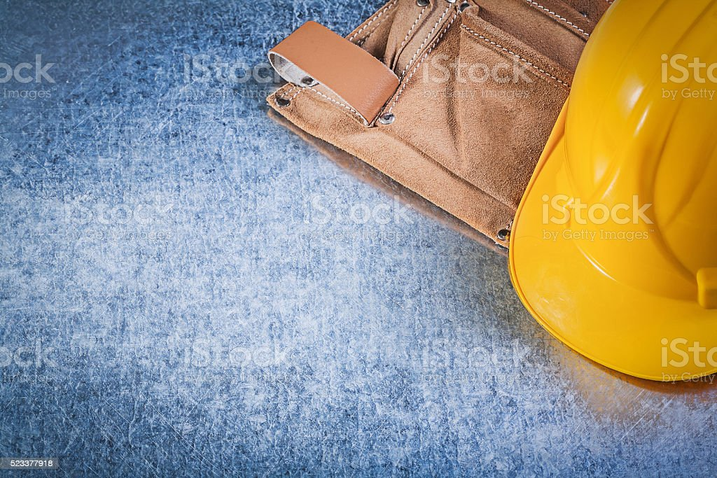 Tool belt safety hard hat on metallic background construction co stock photo