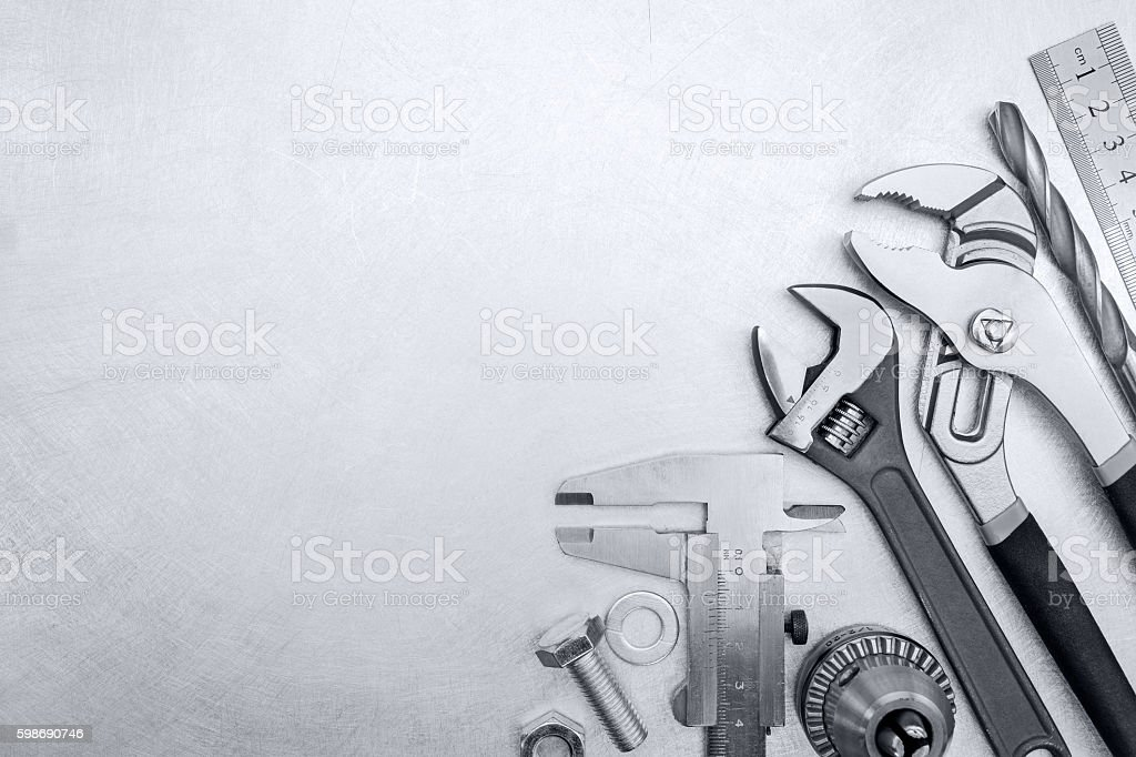 tool set of adjustable wrenches, drill, ruler on scratched metal stock photo