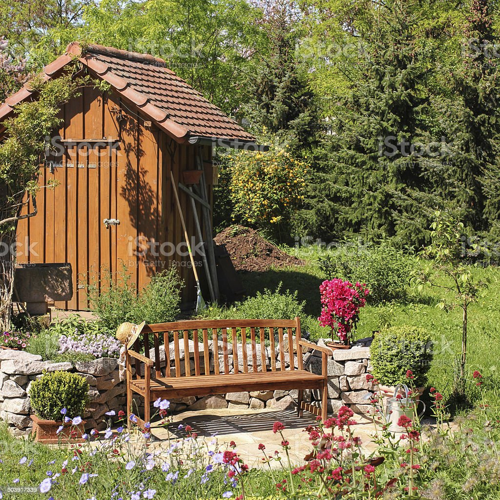 Tool shed and seat in the garden stock photo