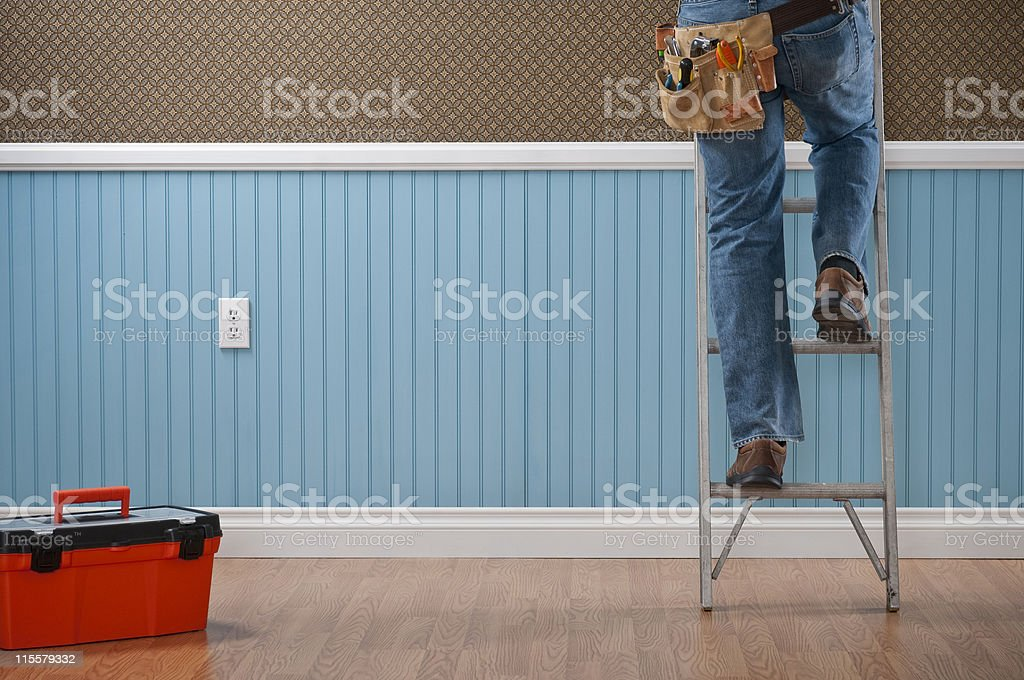 Toolbox and legs of a handyman climbing a ladder stock photo
