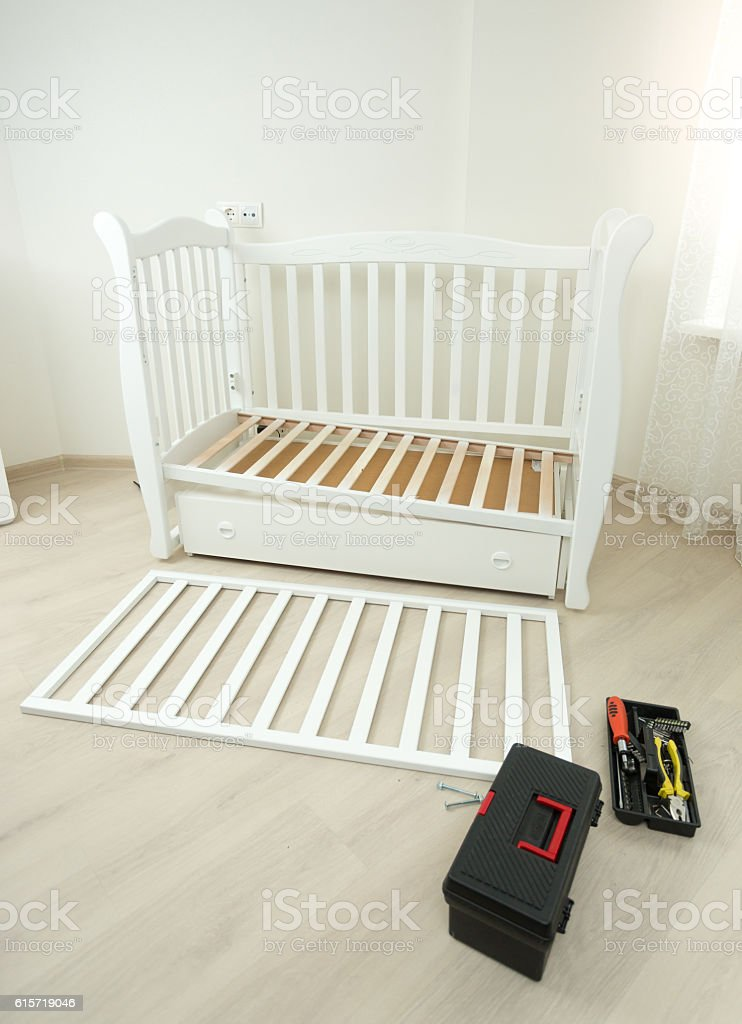 Tools box lying on floor next to disassembled baby bed stock photo