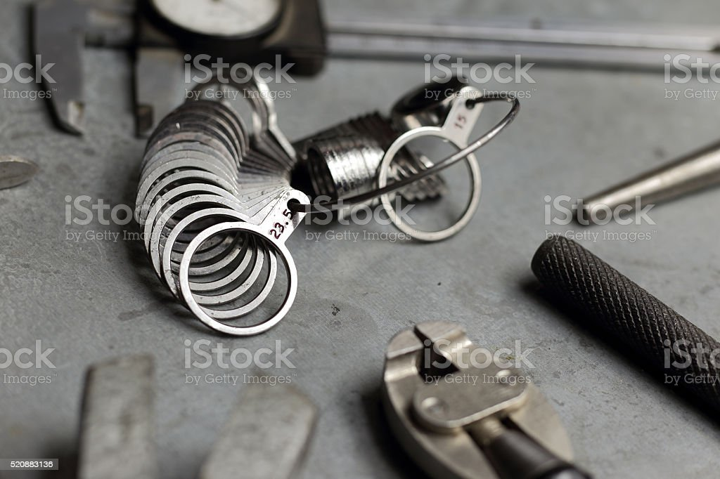 Tools of jewellery. Jewelry workplace metal background. Finger sizing stock photo