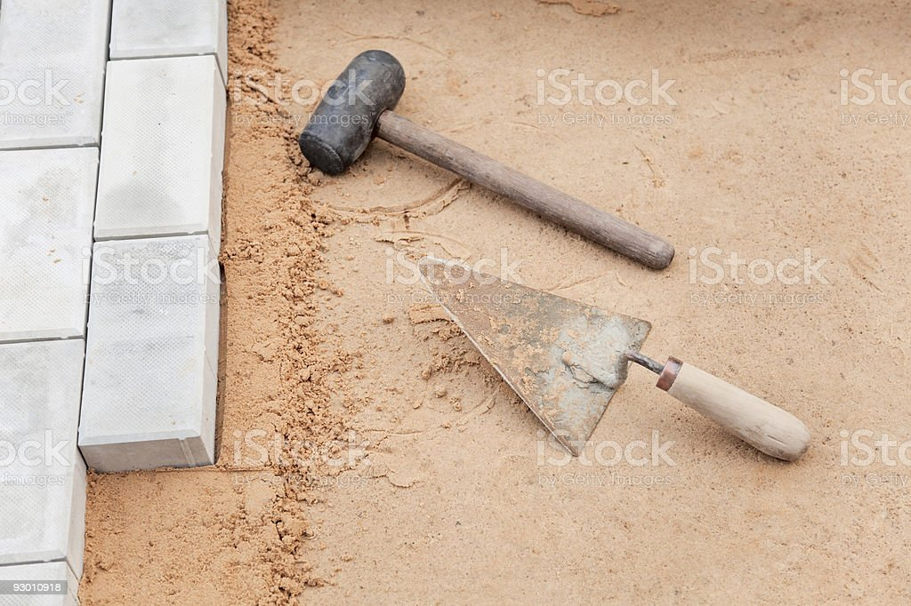 Tools of mason on a sand - trowel and hammer royalty-free stock photo
