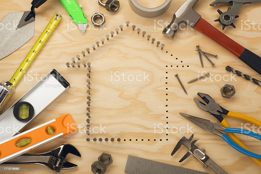 Tools surrounding nails in house shape stock photo