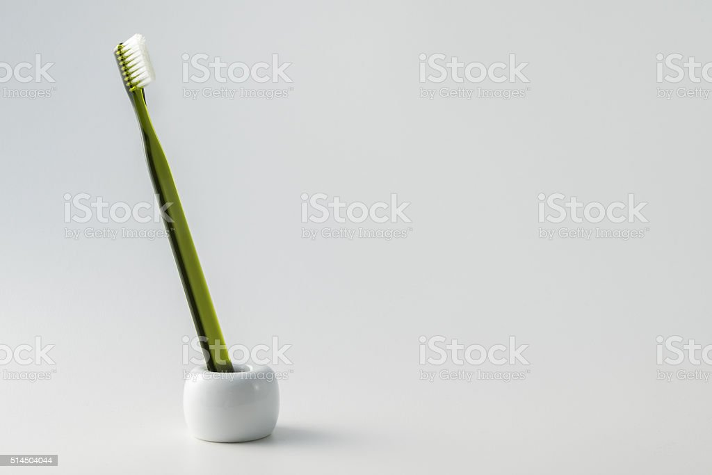Toothbrush in holder on white background stock photo