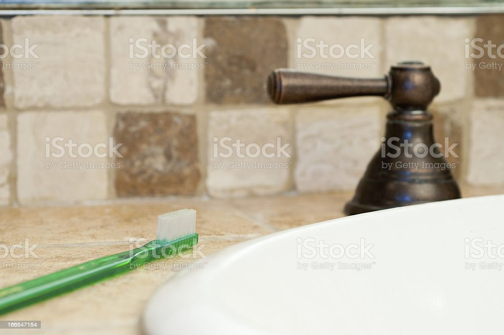 Toothbrush on Bathroom Counter Next to Faucet royalty-free stock photo