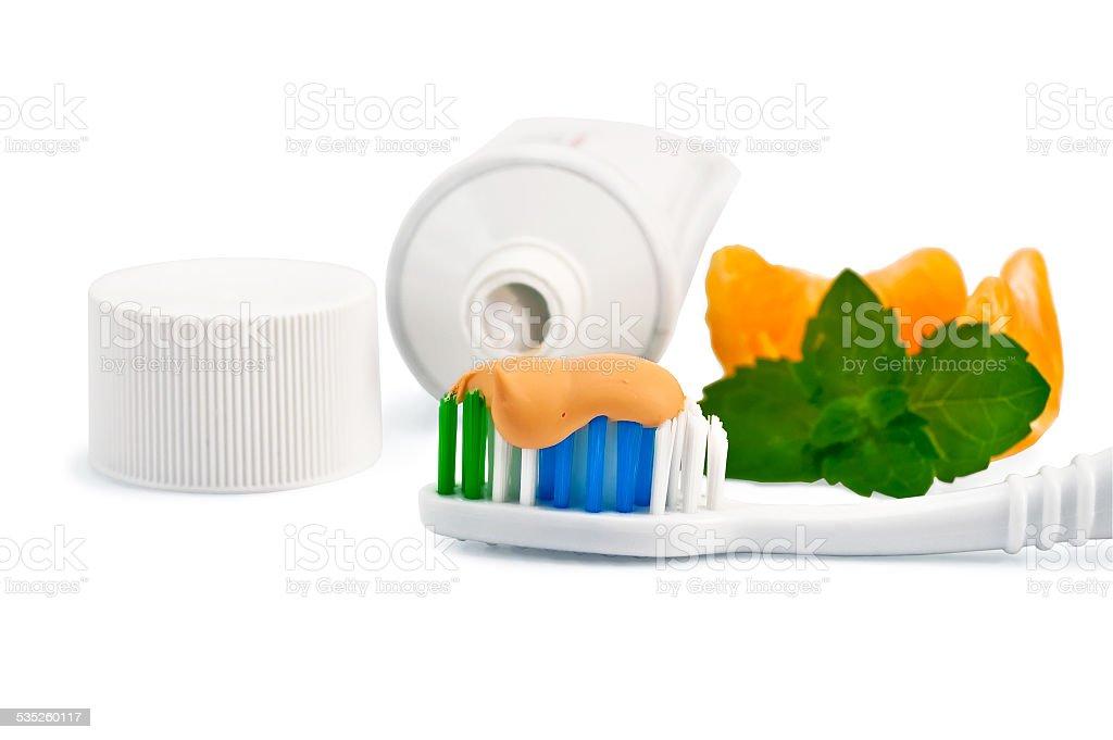 Toothbrush with orange toothpaste stock photo