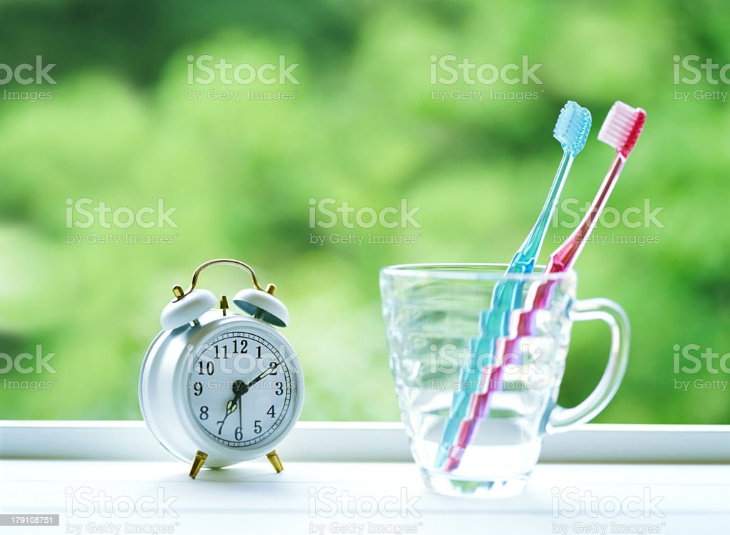Toothbrushes and alarm clock on a window sill stock photo