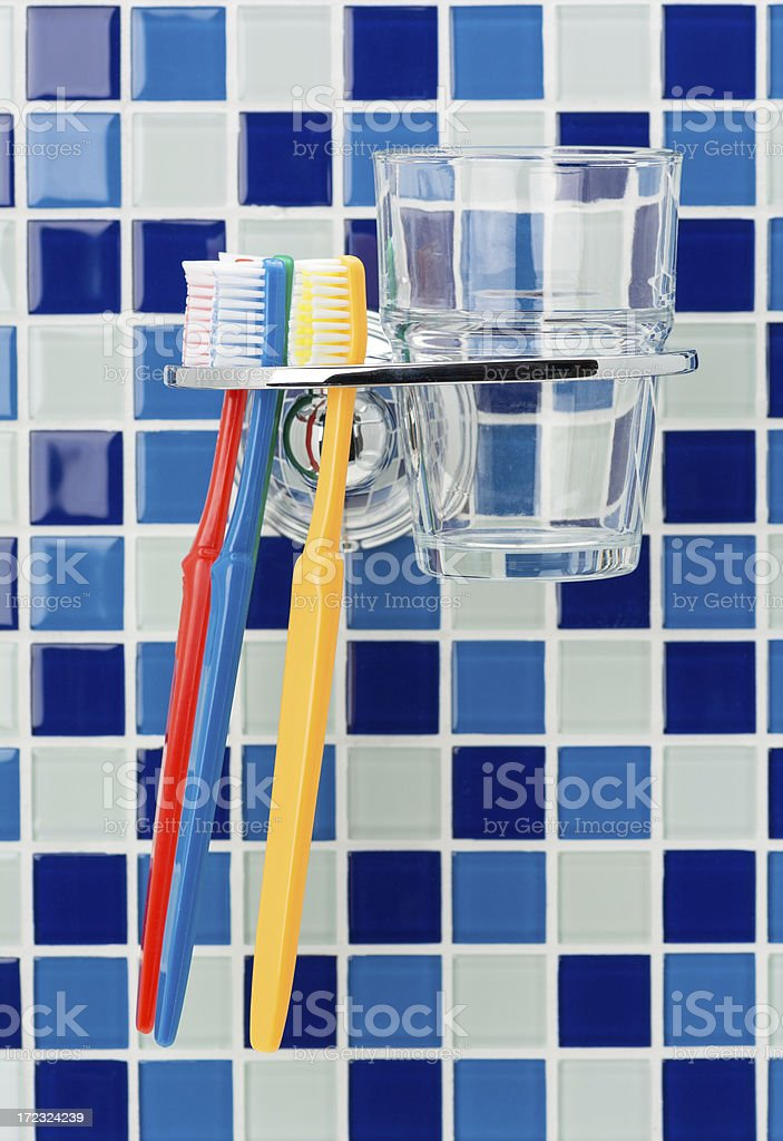 Toothbrushes and holder on a tiled wall royalty-free stock photo