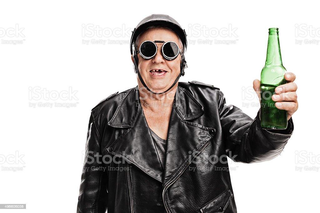 Toothless senior biker holding a bottle of beer stock photo