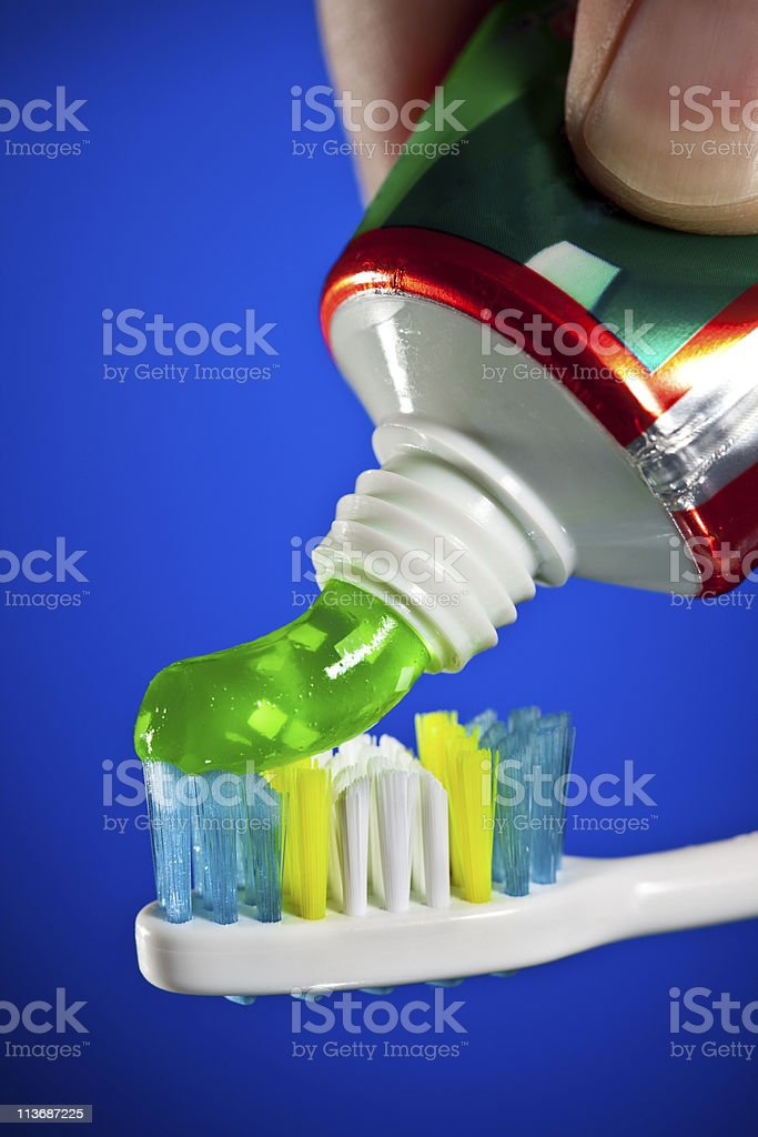 toothpaste being squeezed onto a toothbrush stock photo