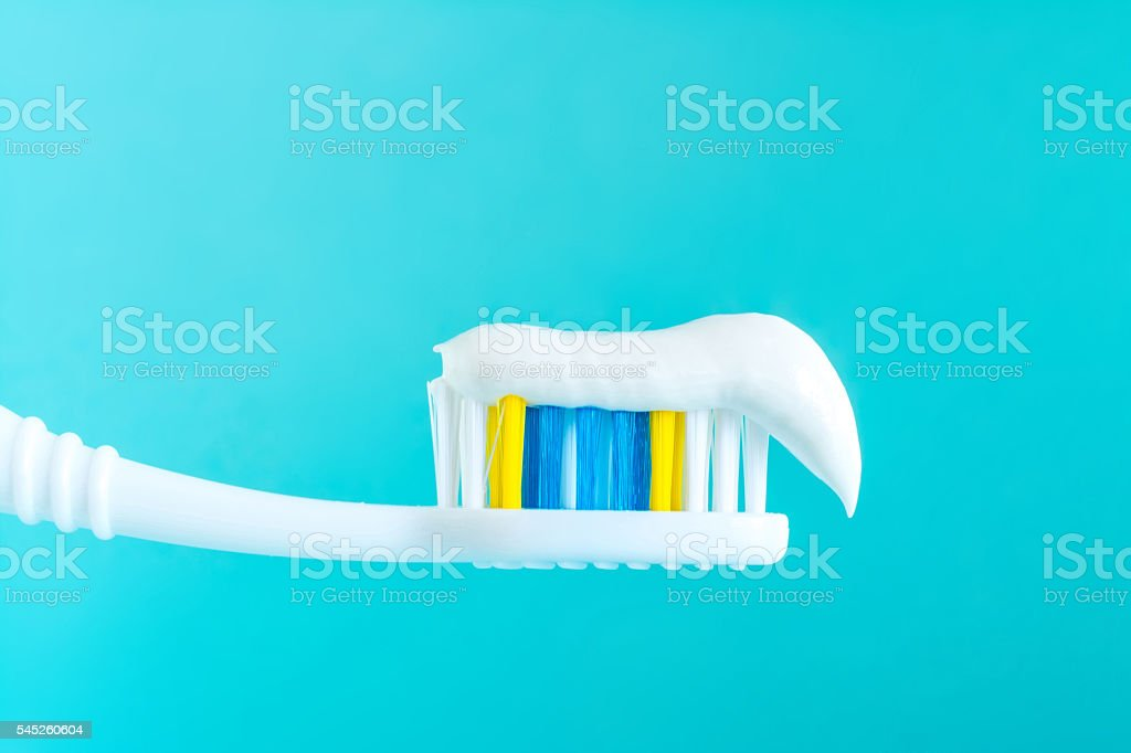 Toothpaste on a toothbrush close-up on a blue background stock photo