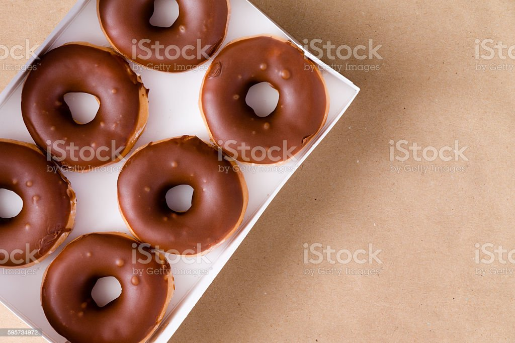 Top down view of chocolate and cream donuts in box stock photo