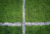 Top down view of white line on green soccer field.