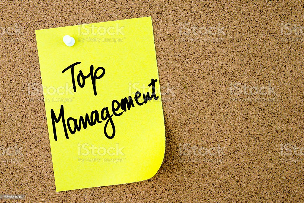 Top Management text written on yellow paper note pinned on cork board...