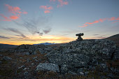Top marked pile of stones with vibrant yellow sunset background
