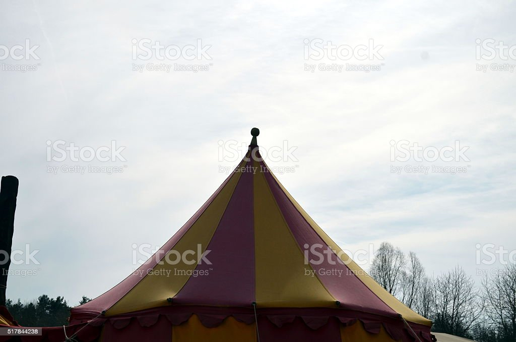top of a medieval circus tent colorful with blue sky stock photo