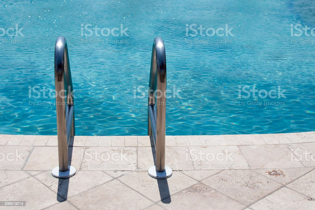 Top of a metal ladder into a pool stock photo