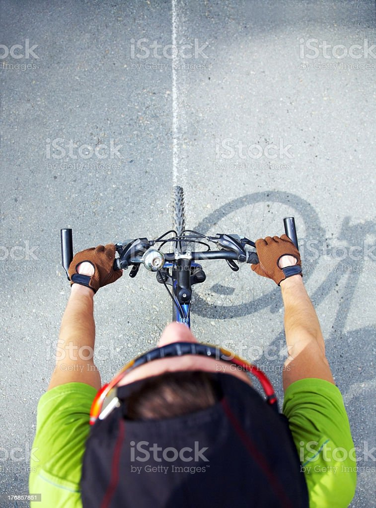 Top of a person's head and handlebars as they ride a bike stock photo
