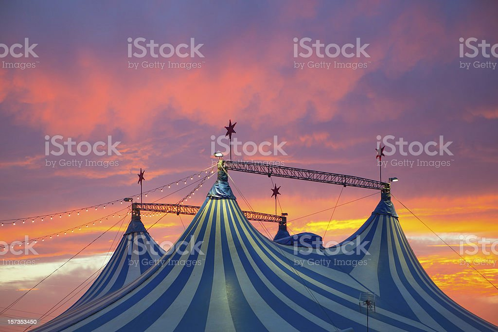 Top of blue and white circus tent against a vivid sunset stock photo
