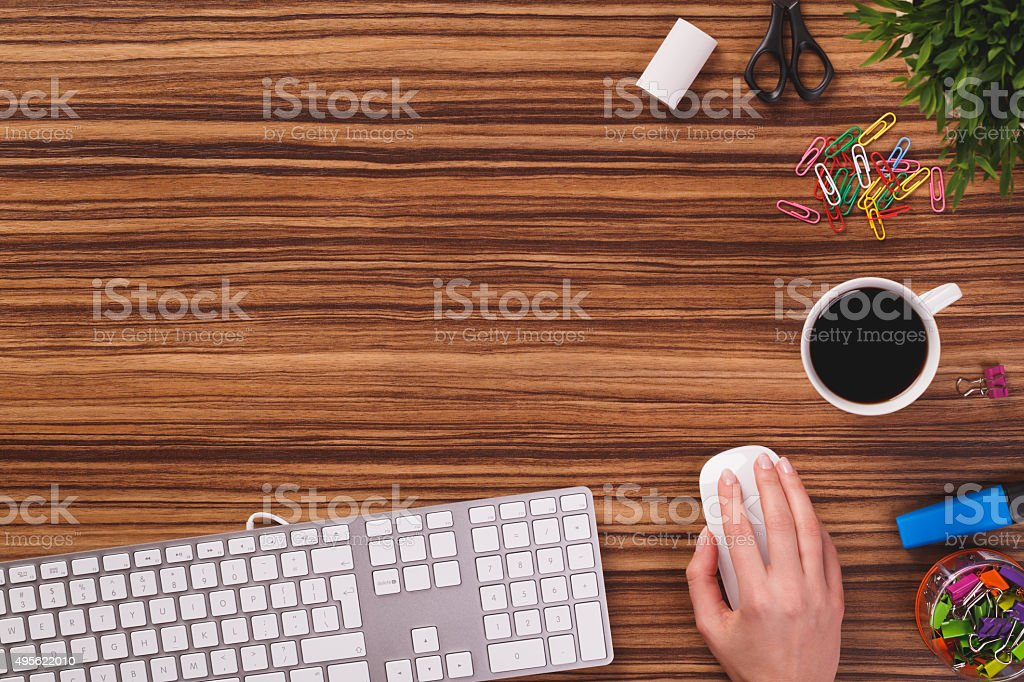 Top of desk with mouse, hand using mouse. stock photo