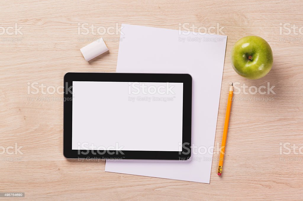 Top of desk with tablet, paper, pencil, apple, eraser. stock photo