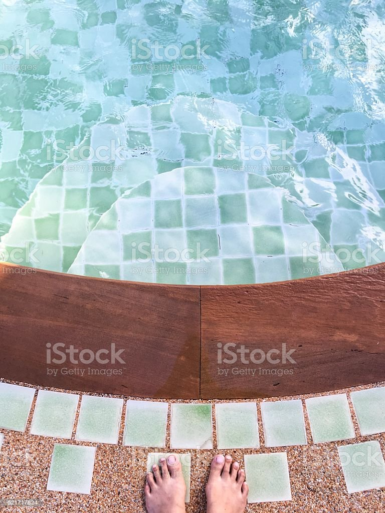 Top of lady feet standing over swimming pool royalty-free stock photo