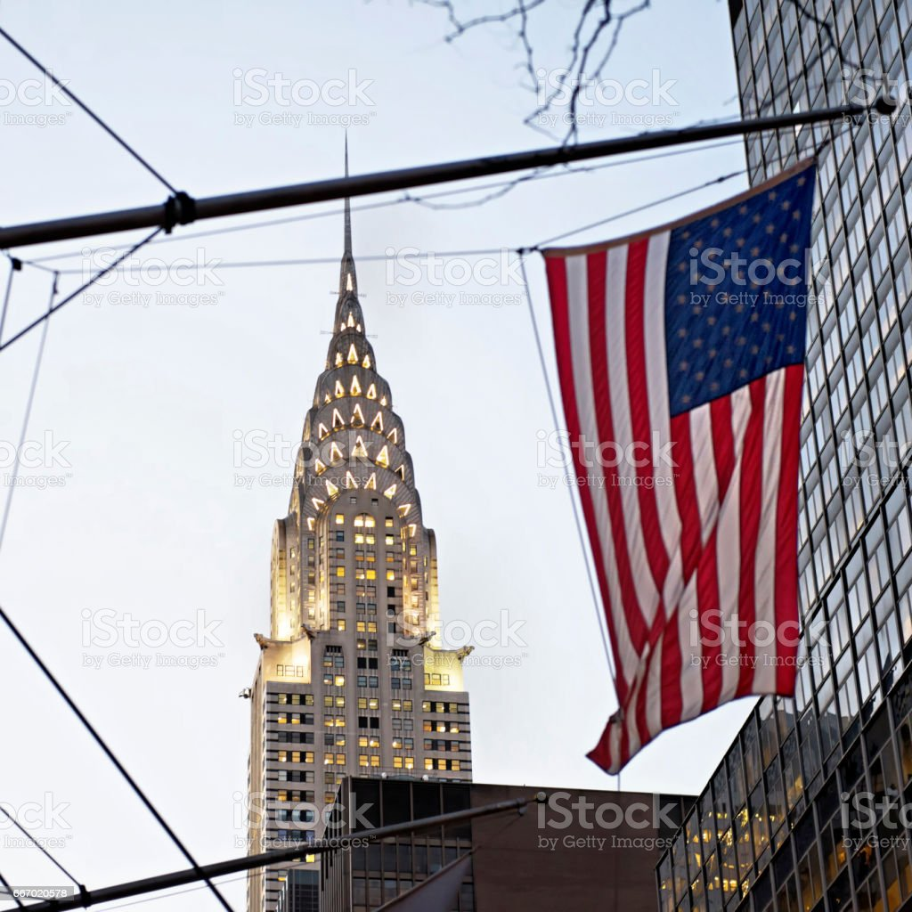 Top of the Chrysler Building and the  American flag in New York City,USA stock photo