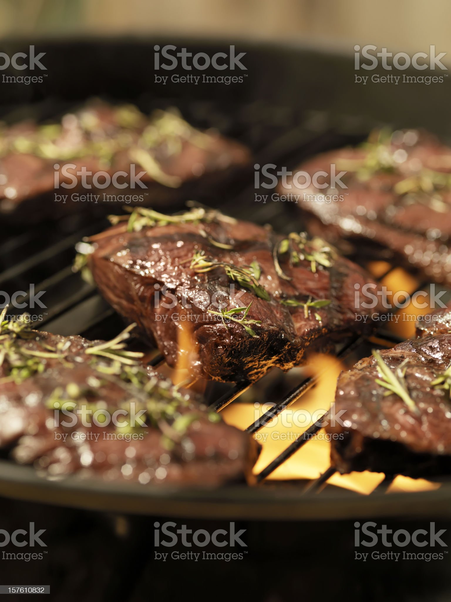 Top Sirloin Steaks with Fresh Herbs on an outdoor BBQ royalty-free stock photo