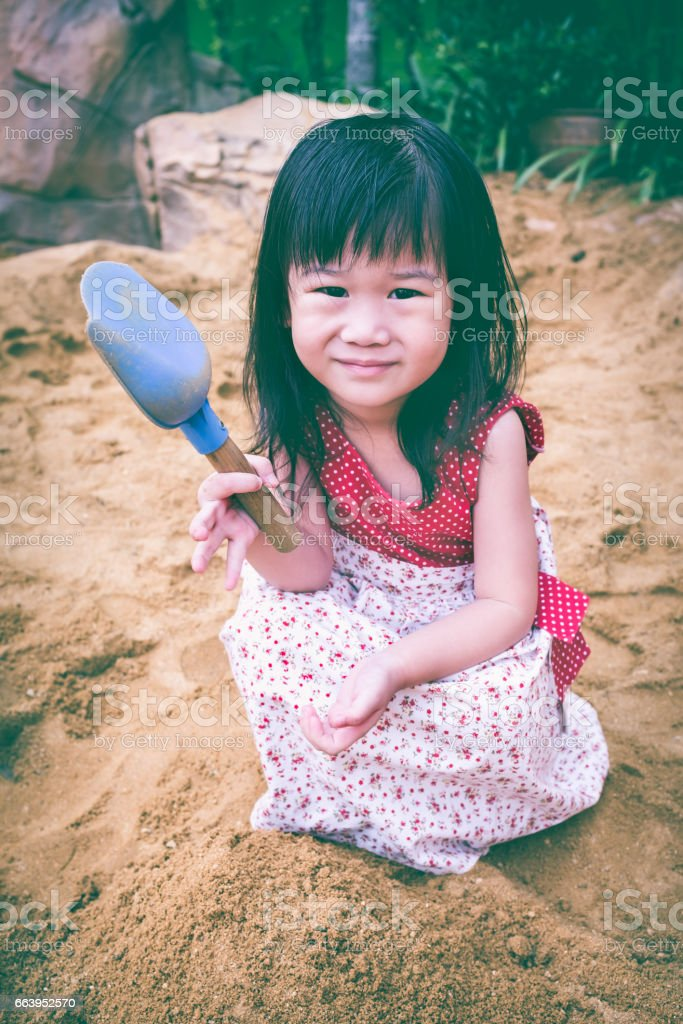 Top view. Adorable asian girl has fun digging in sand. stock photo