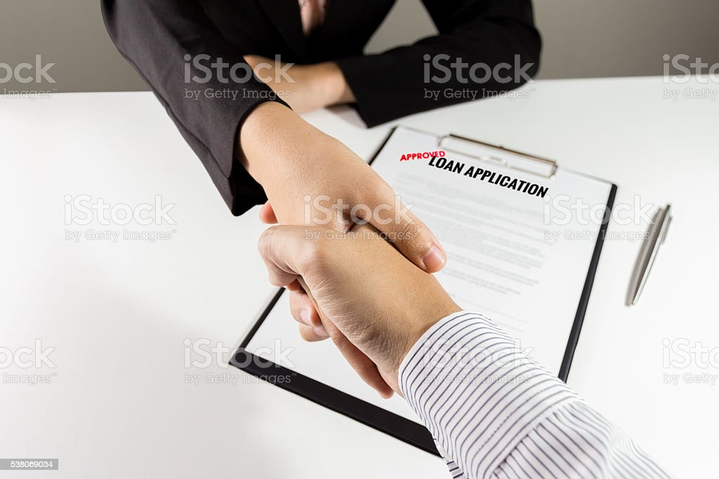 Top view banker and customer handshake over the loan application stock photo