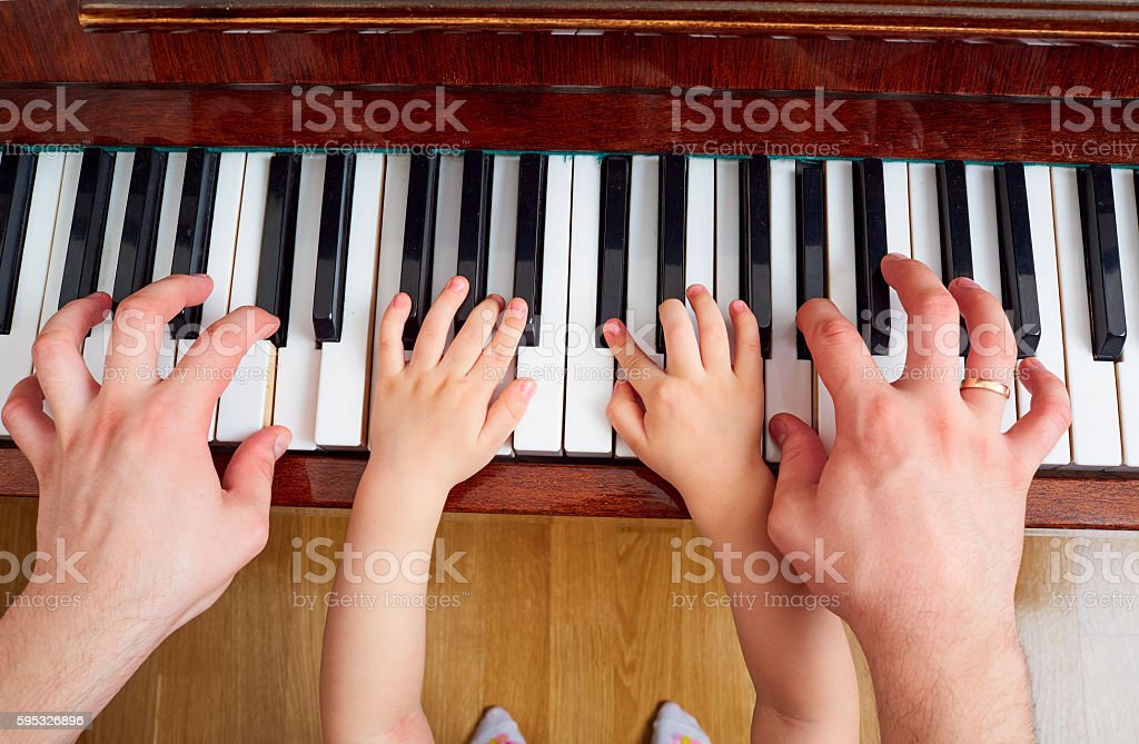 Top view close-up of hands  father and child on  piano stock photo