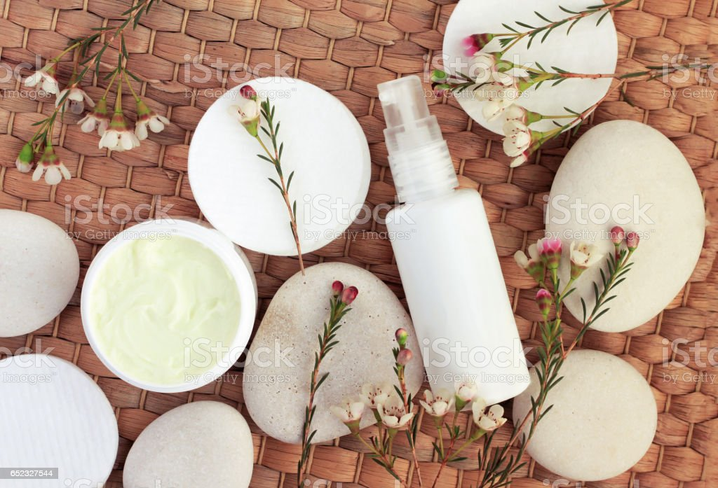 Top view cosmetic herbal products on strawmat background. stock photo