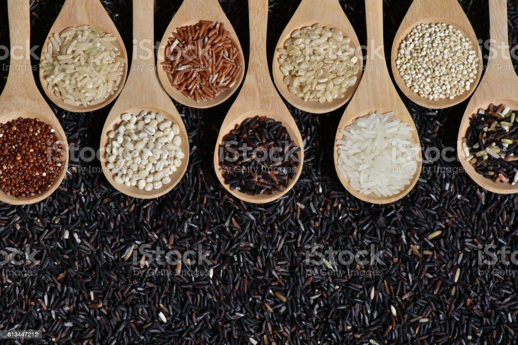 Top view different rice on wooden scoop with black riceberry stock photo