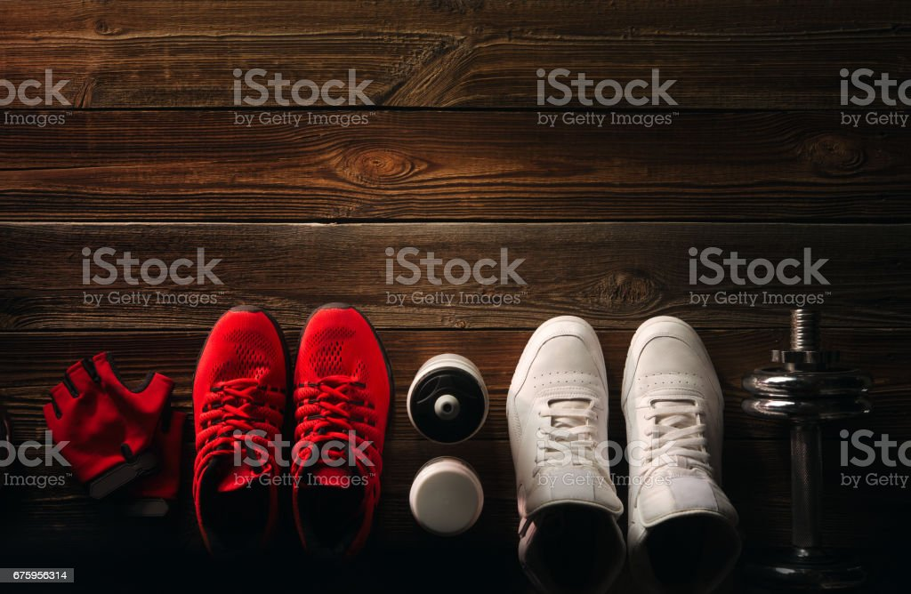 Top view Fitness equipment and supplements on wooden floor in gym Fitness background with Pair of Sneakers Water bottle Separate dumbbell plates Kettlebell Red Gloves Supplements bottle stock photo