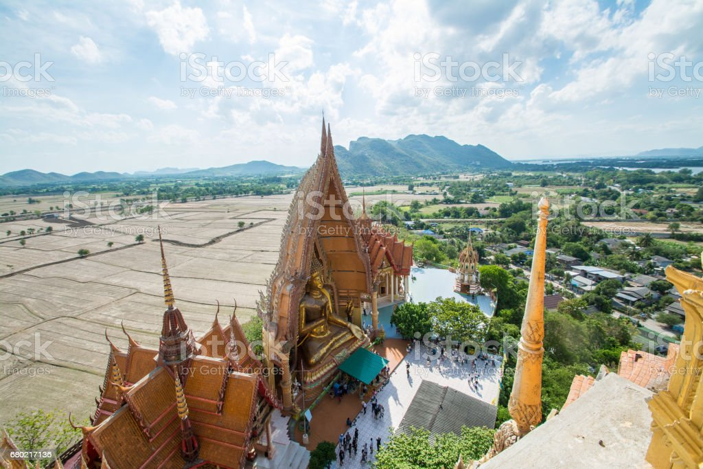 Top view from the pagoda, golden buddha statue with rice fields and mountain background, Wat Tham Sua(Tiger Cave Temple),  Kanchanburi, Thailand stock photo