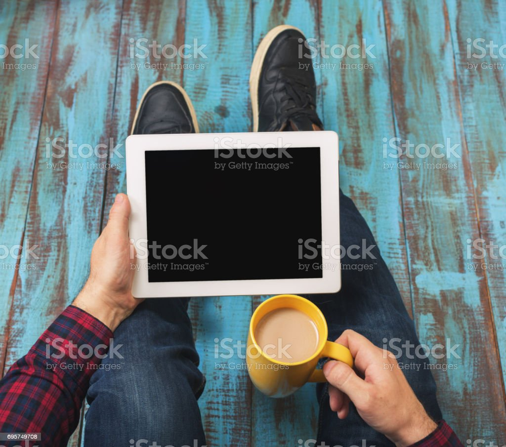 Top view image of man holding digital tablet with copy space and cup of coffee while sitting at the floor stock photo
