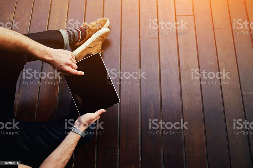 Top view male student using touchpad while sitting on floor stock photo