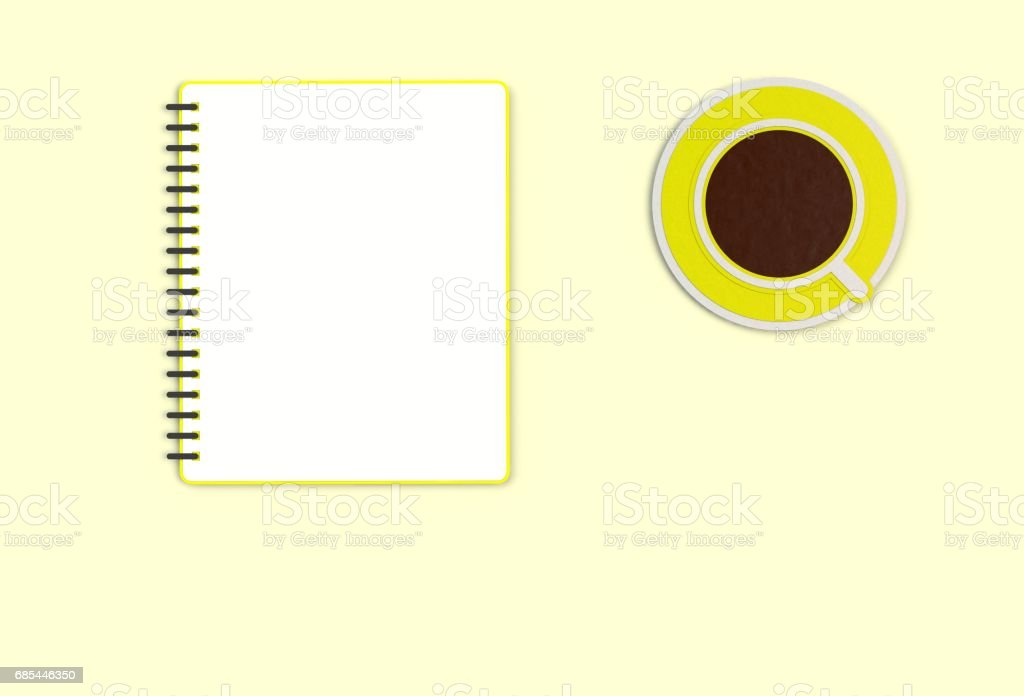 Top view notebook with cup of coffee on yellow desk, paper art and craft style. stock photo