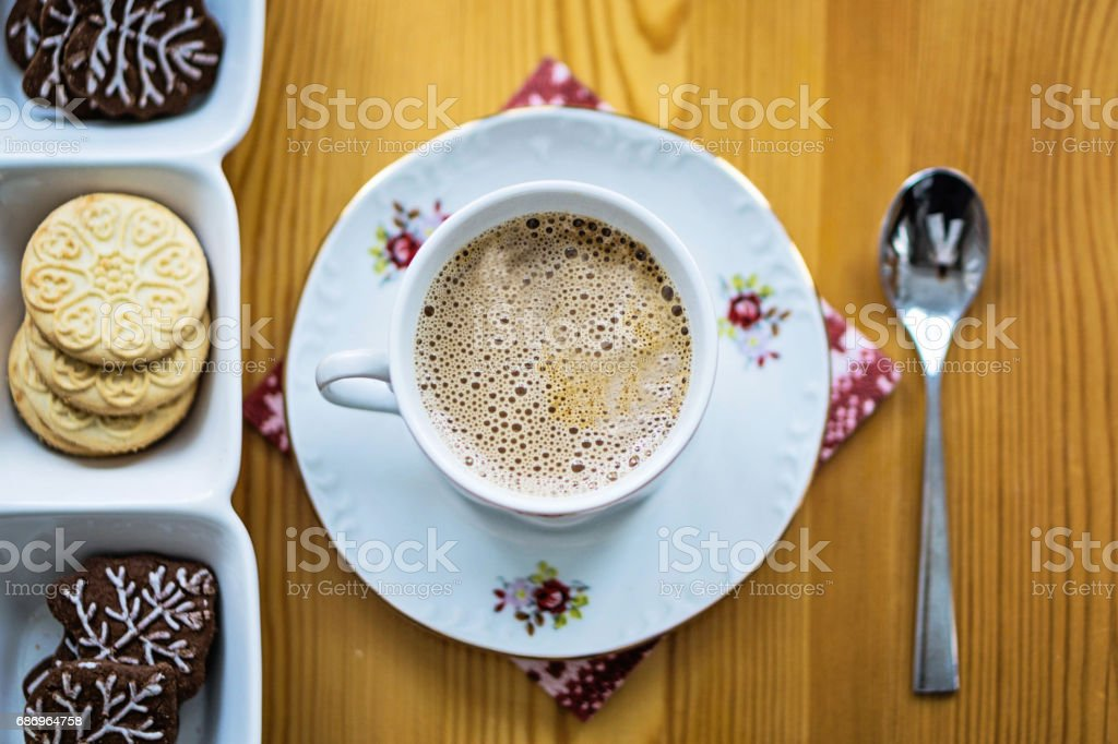 Top view of a cup of coffee, cookies and a spoon at kitchen table. stock photo