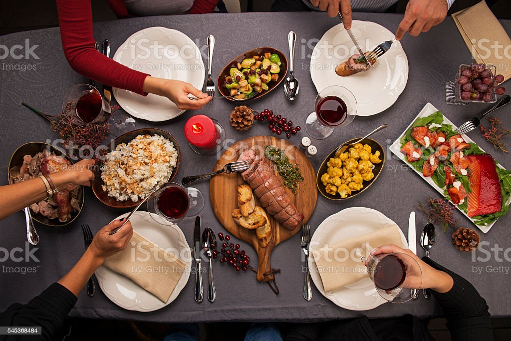 Top view of a dinner table and hands serving food stock photo