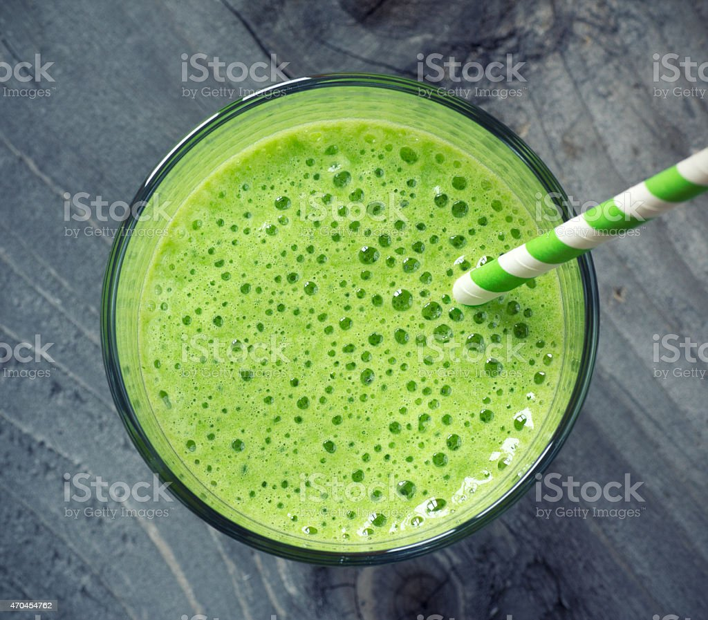 Top view of a glass of green smoothie with green straw stock photo