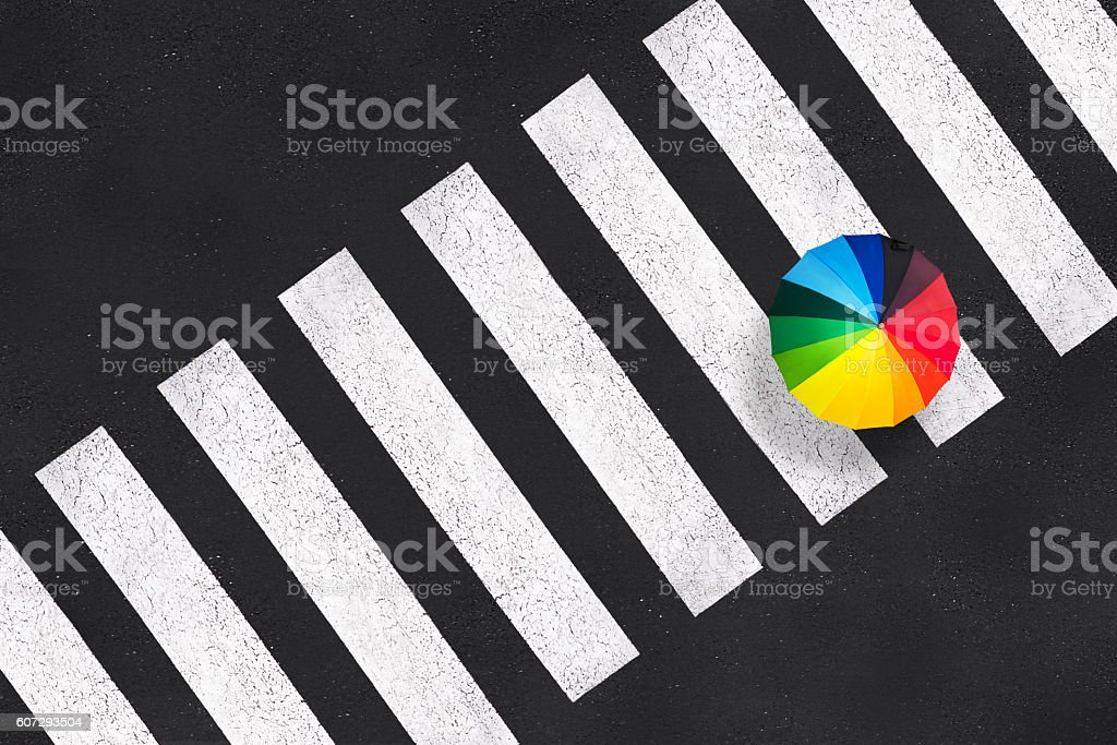 Top view of a rainbow umbrella on a pedestrian crosswalk stock photo