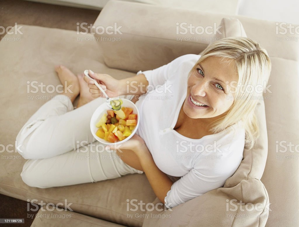 Top view of a relaxed mature woman on couch eating royalty-free stock photo