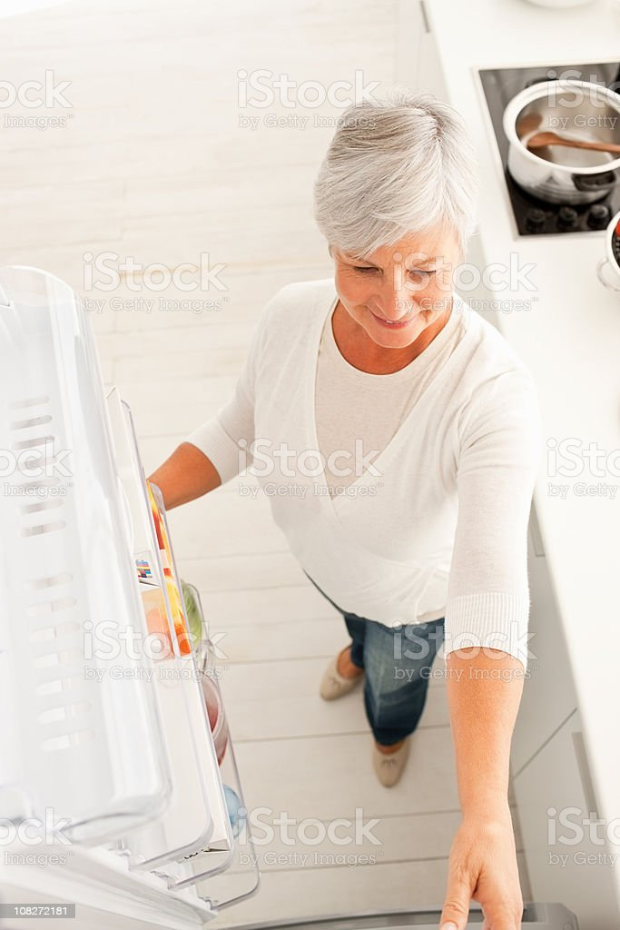 Top view of a senior woman opening refrigerator royalty-free stock photo